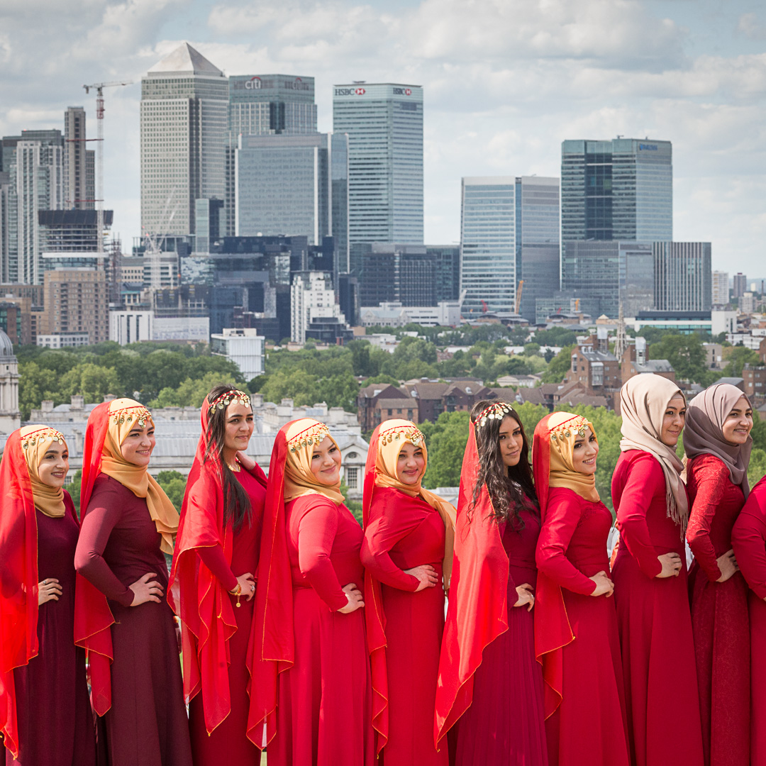 Wedding party poses in front of Canary Wharf from Greenwich Park