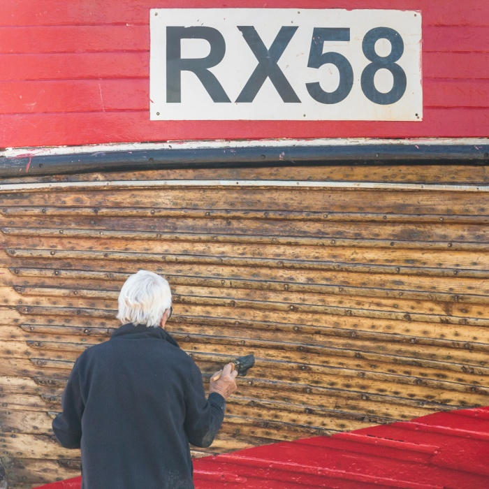RX58 having her hull varnished, The Stade, Hastings, Sussex.