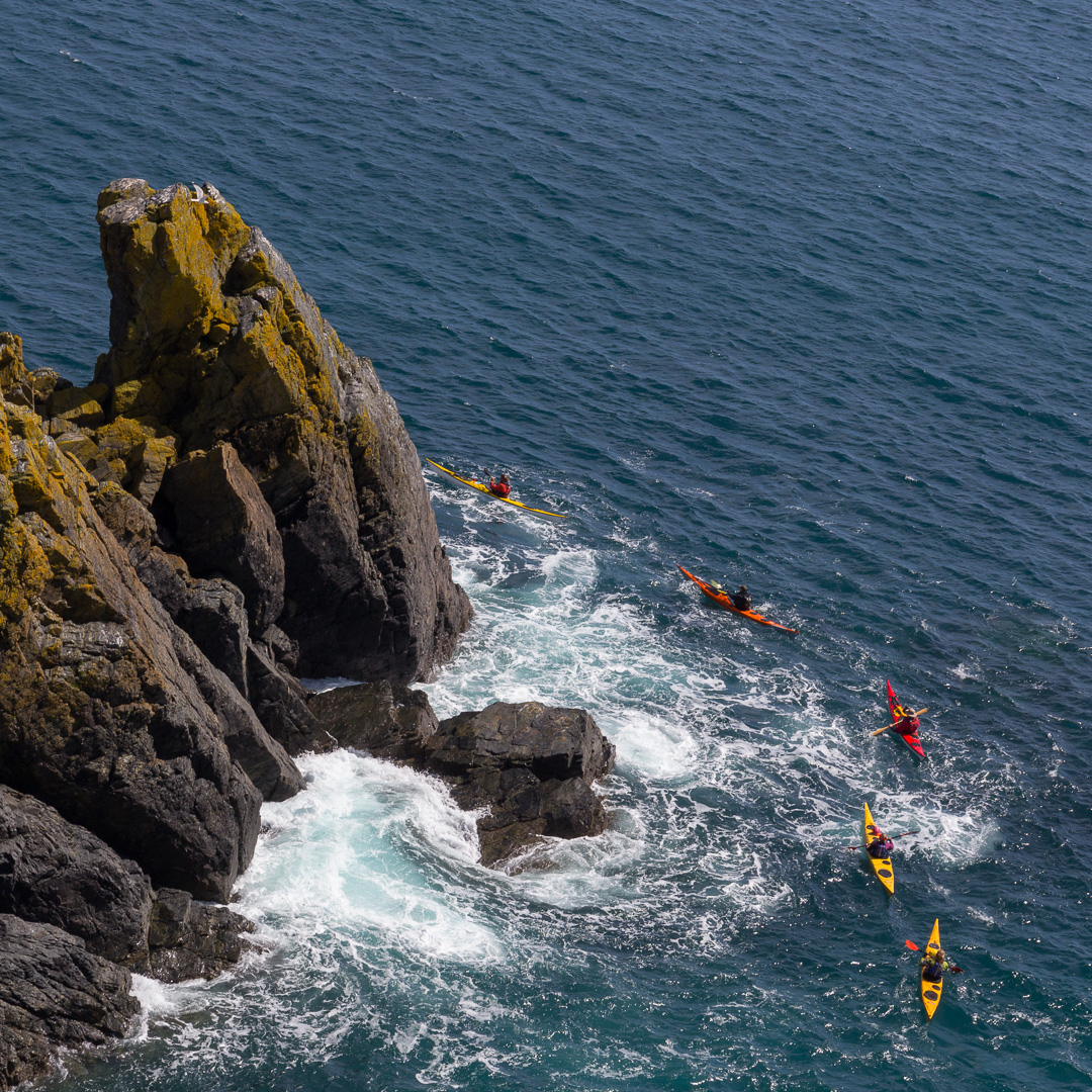 Kayakers pass the Colt, Cadgwith, Cornwall.