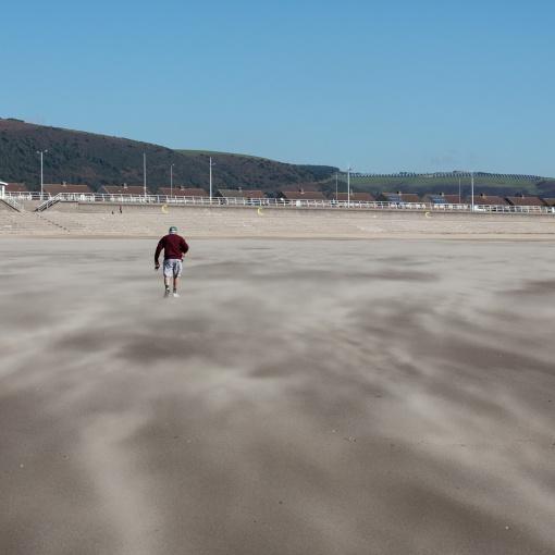 Lifting a dog out of blown sand, Aberavon Sands, Port Talbot, Glamorgan.