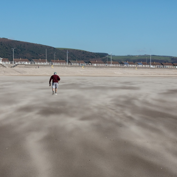 Lifting a dog out of blown sand, Aberavon Sands, Port Talbot, Glamorgan.