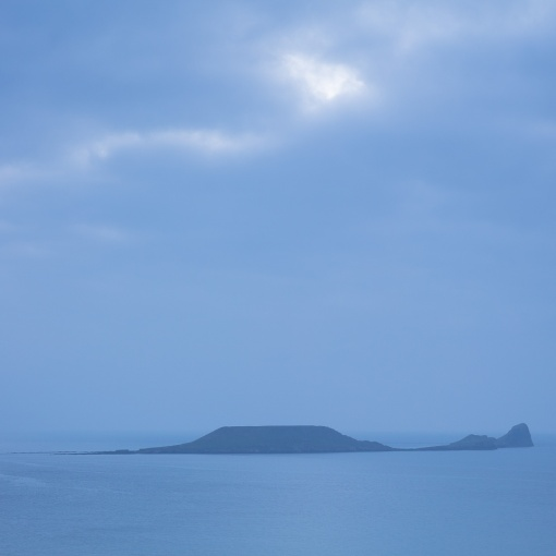 Last Light, Worm's head on a rising tide. Named 'Wurm' meaning 'dragon' by Viking invaders. Gower, Glamorgan.