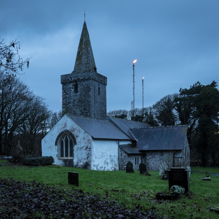St Mary's Church with Pembroke Oil Refinery Flares, Pwllcrochan, Pembrokeshire.